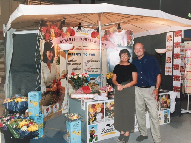 Photograph of Sandra and Erik under an umbrella at the Post Office trade show